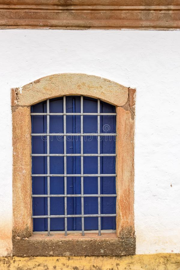 Old church window made of wood in colonial style with frame in stone in Sabara city stock photo