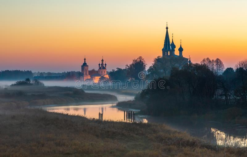 Old churches  at fog sunrise in Dunilovo. Russia royalty free stock photo
