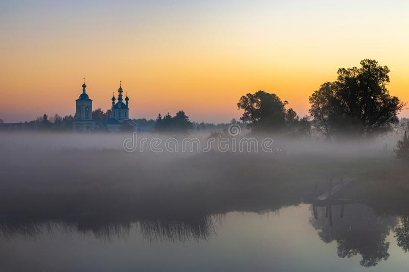 Old churches  at fog sunrise in Dunilovo. Russia stock image