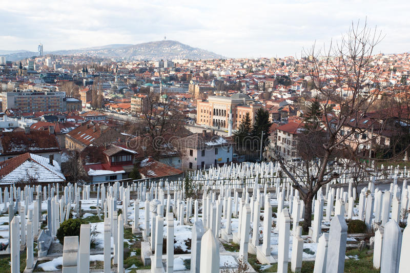 Old City Hall background & the cemetery on the hill of Sarajevo. SARAJEVO, BOSNIA AND HERZEGOVINA: Old City Hall background & the cemetery on the hill. Total royalty free stock photo