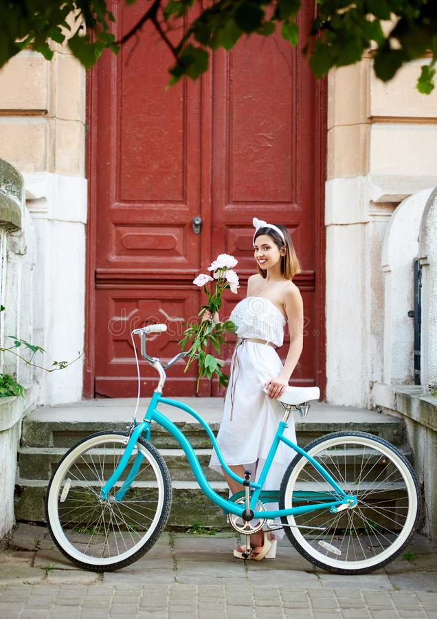 Old city. Lovely girl with retro bicycle and bouquet peonies stock photos