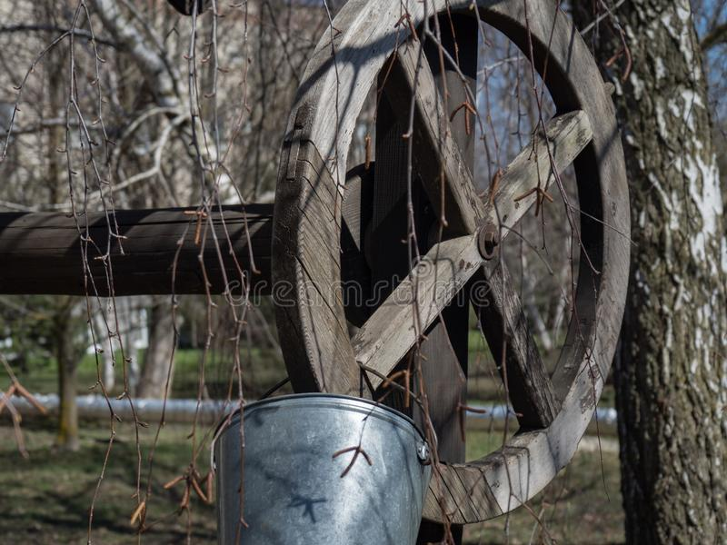 City park trees branch spring day well old yard bucket for drinking abandoned wooden bar stock photo