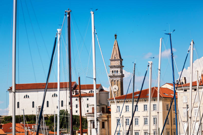 Old city Piran in Slovenia. View vith St. George`s Parish Church. Through masts of yachts moored in a bay. Summer time stock image