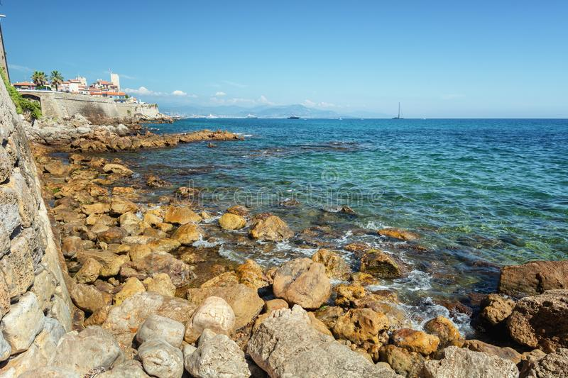 The old city wall along the coast of the French town of Antibes with the old old center in the distance.  royalty free stock image