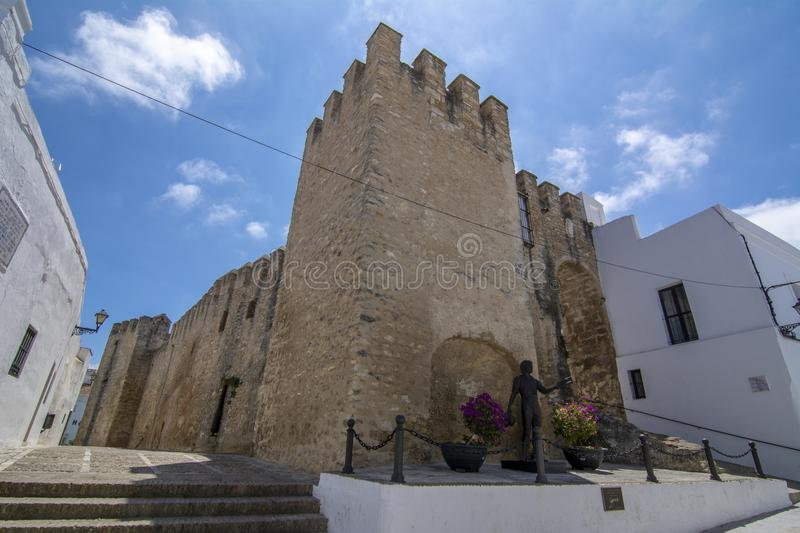 Old city wall with gate of Vejer de la Frontera in Spain. Vejer de la Frontera, Andalucia, Spain, July 2017: Part of the castle wall battlements of Vejer de la royalty free stock images
