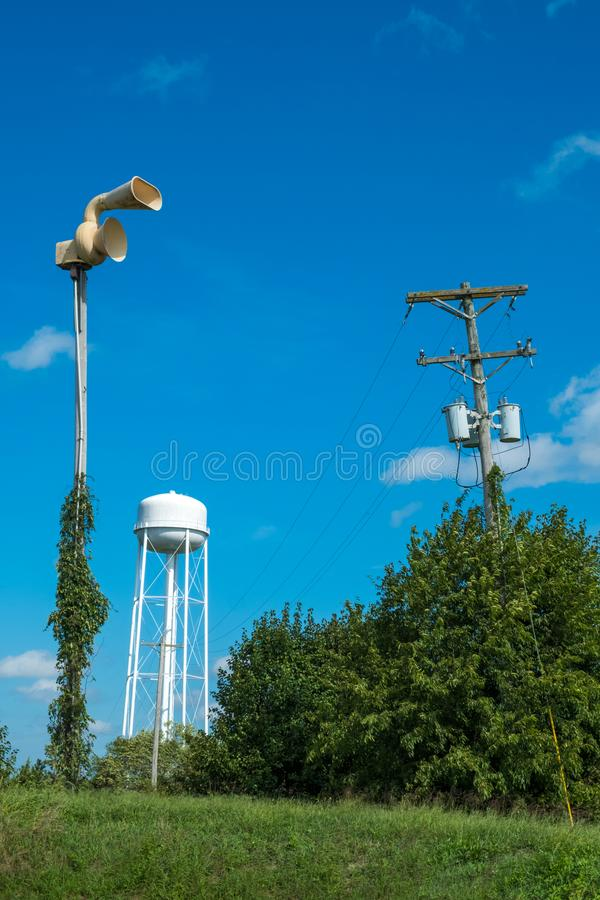 Old civil defense siren, old water tower and utility pole/old in. Frastructure in a small rural town royalty free stock photo