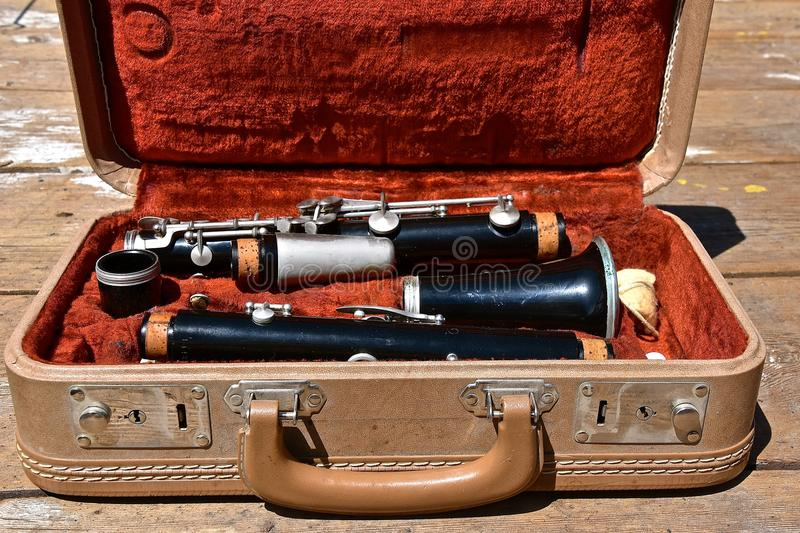 Old clarinet in carrying case. An old vintage clarinet is stored in a vintage carrying case stock image