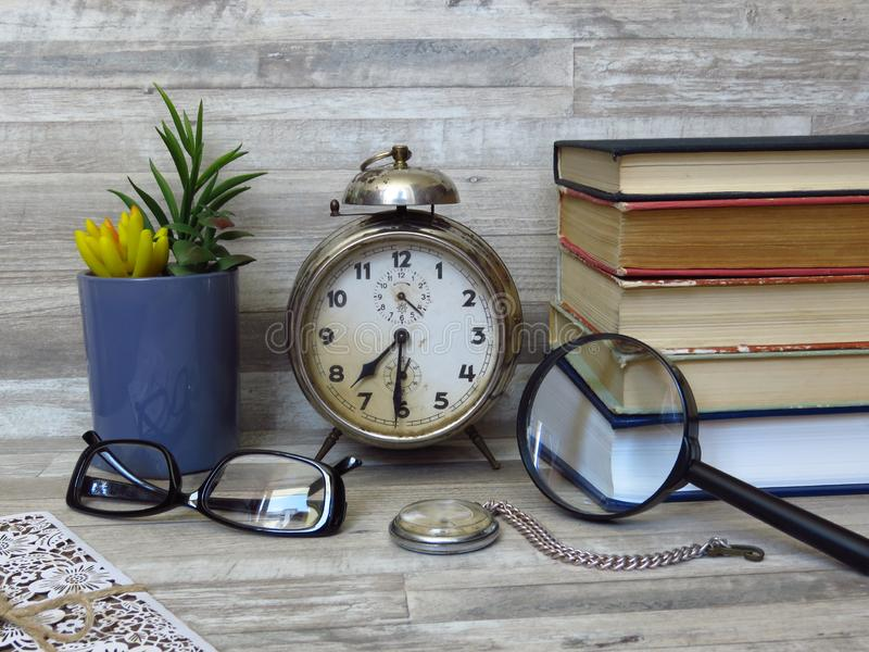 Old Classic Alarm Clock, Pocket Watch, Hand-Held Reading Magnifier, a Pair of Glass. Time. Eye Health & Vision. Retro style. royalty free stock image