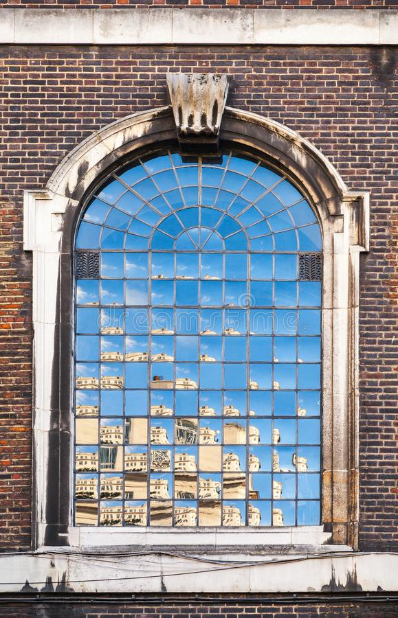 Old classic arched window in dark brick wall. London, United Kingdom royalty free stock photography