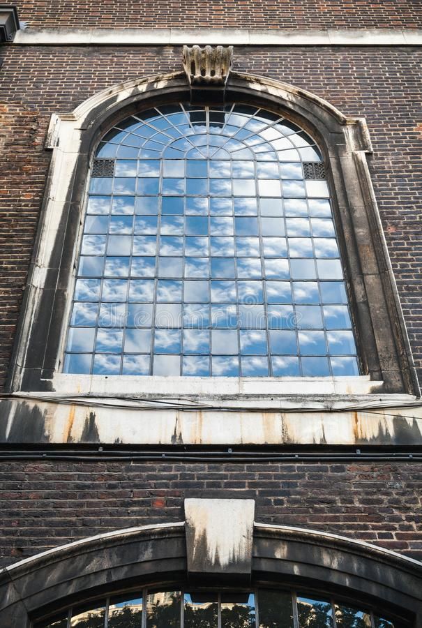 Old classic arched window perspective. In dark brick wall, London, United Kingdom stock images