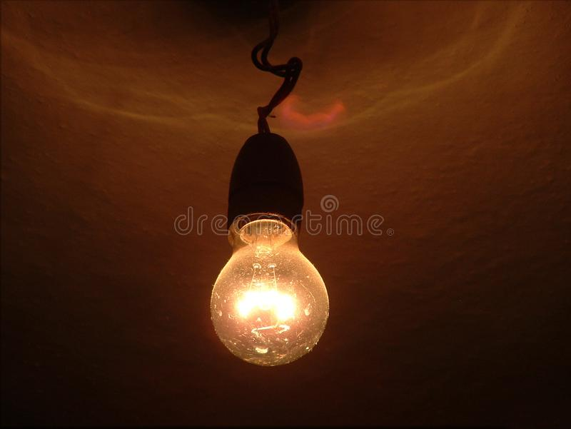 Classic incandescent light bulb powered on. Old classic incandescent light bulb, powered on in an old house. Inefficient compared to led or fluorescent bulbs royalty free stock photo