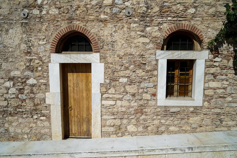 Old classic little church arch door and window frame on earth tone natural stone wall facade background with marble curb in front stock images