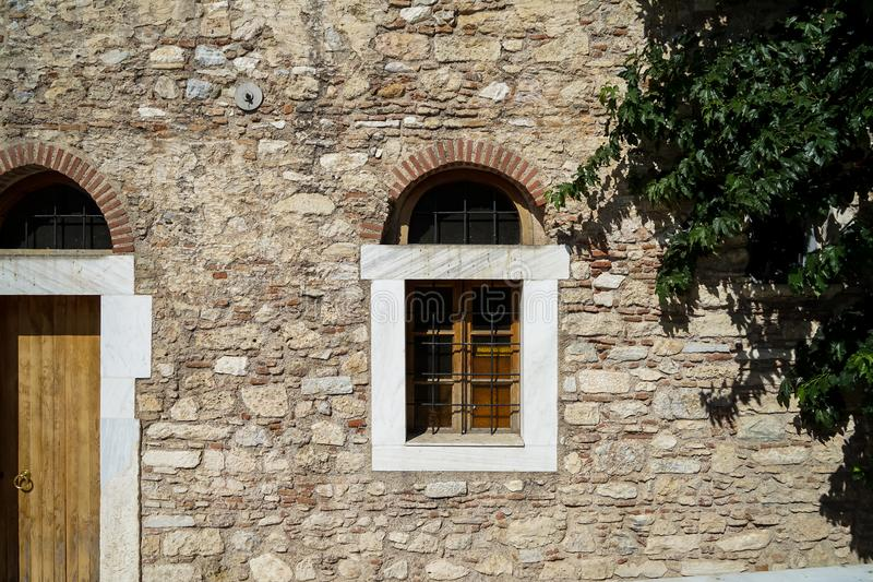 Old classic little church arch window and door frame on earth tone natural stone wall facade background with green tree leaves stock photo