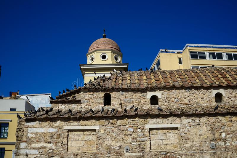Old classic little church in earth tone natural stone with pigeons on terracotta roof tile with clear blue sky and modern building. Background, Athens, Greece stock photos