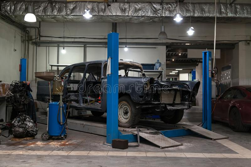 An old classic retro car of black color stands on a blue lift for repair, restoration and restoration in a vehicle maintenance and. Tuning workshop. Auto royalty free stock images