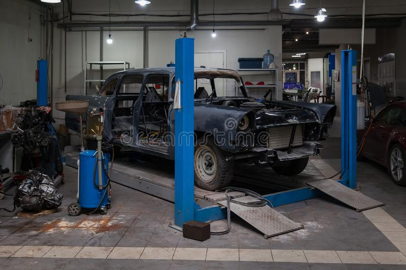 An old classic retro car of black color stands on a blue lift for repair, restoration and restoration in a vehicle maintenance and. Tuning workshop. Auto stock photography