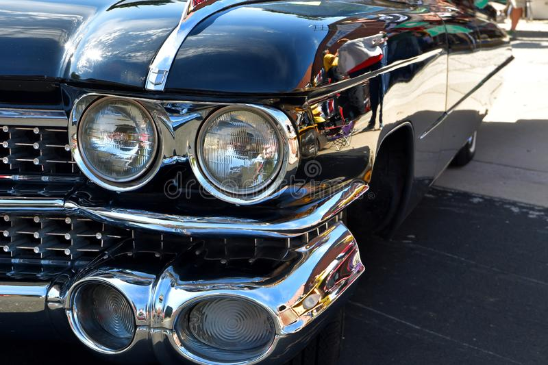 An old classic vintage retro automobile with big headlamps, front grill,  and lights royalty free stock photography