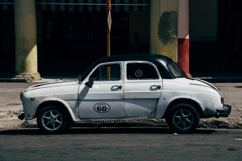 A old classic Fiat parked in Havana, Cuba. A old classic white Fiat parked in Havana, Cuba royalty free stock photography