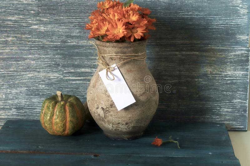 Old clay jug with a bouquet of flowers and pumpkins on a wooden table royalty free stock images