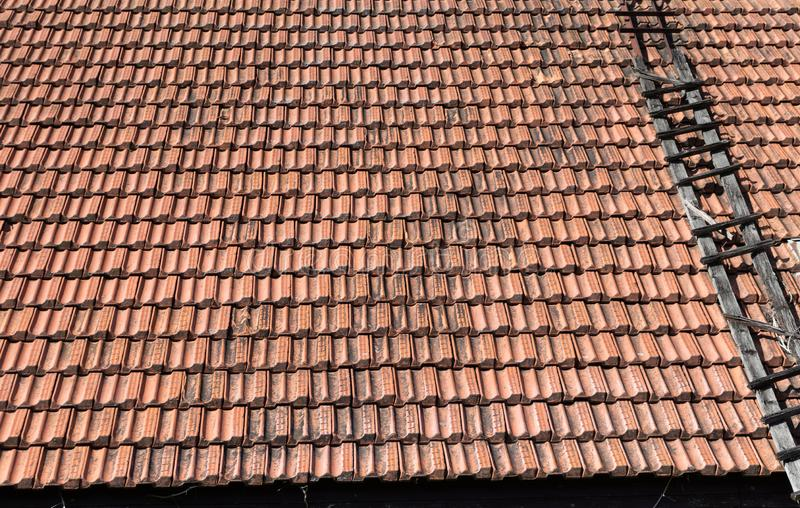 Old clay roof tiles at england house. Material, orange, home, structure, architecture, row, construction, protection, pattern, exterior, detail, red, outdoors royalty free stock images
