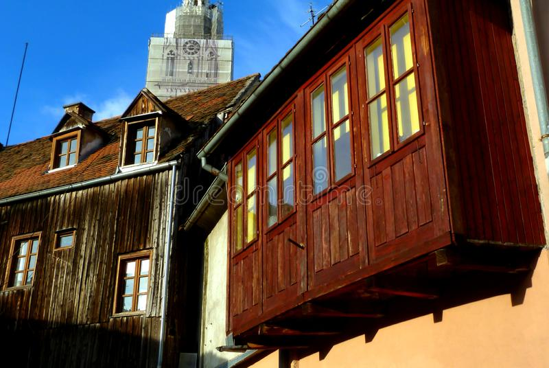 Old wooden facade in downtown Zagreb with dormers and church tower behind. Old clay sloped residential roof in downtown Zagreb. small wooden dormers. aged deep royalty free stock image