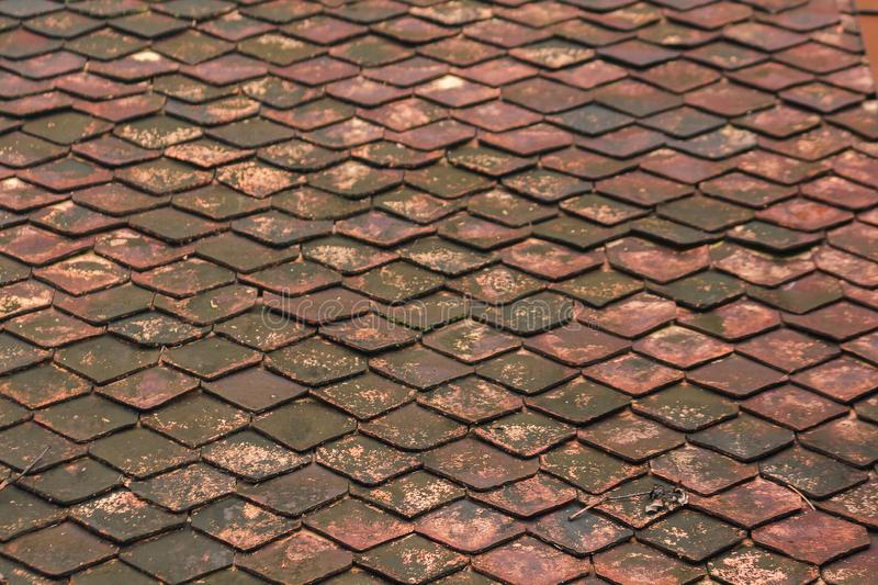 Old clay tiles on the roof with moss. Caused by moisture stock photos