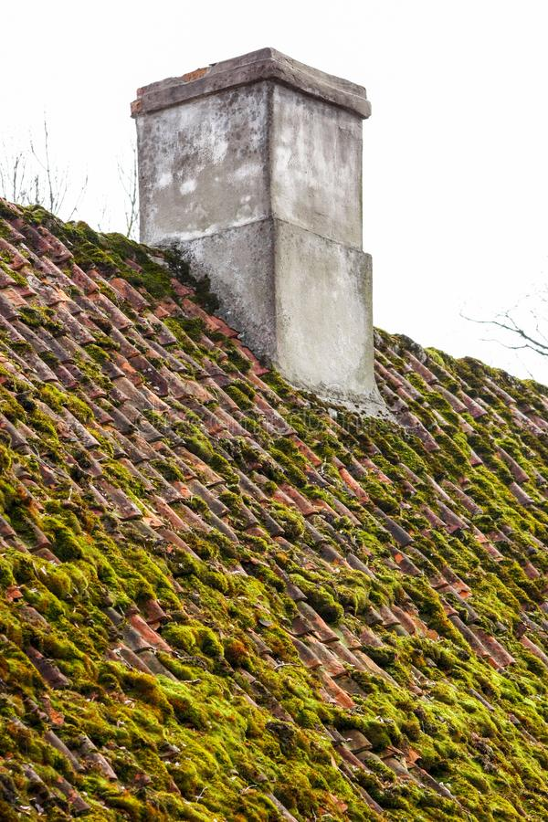 Old clay tiles rooftop with grey masonry chimney. Grey masonry chimney and old clay tiles roof covered with moss in Kuldiga, Latvia royalty free stock images