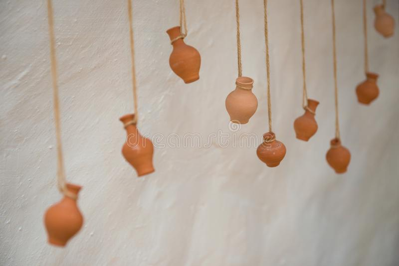 On an old clay wall hang vases on ropes, like decor.  stock images