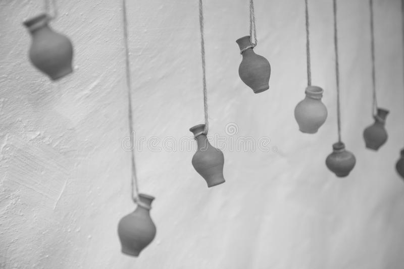 On an old clay wall hang vases on ropes, like decor.  royalty free stock photos