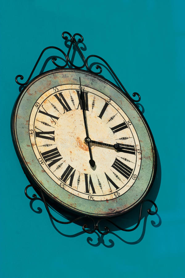 Old clock. Old decorative clock on a blue canvas royalty free stock photos