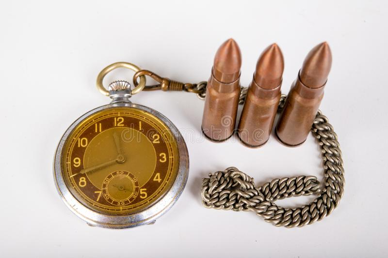 Old clock and ammunition on a white table. Explosive material and time measure stock photo