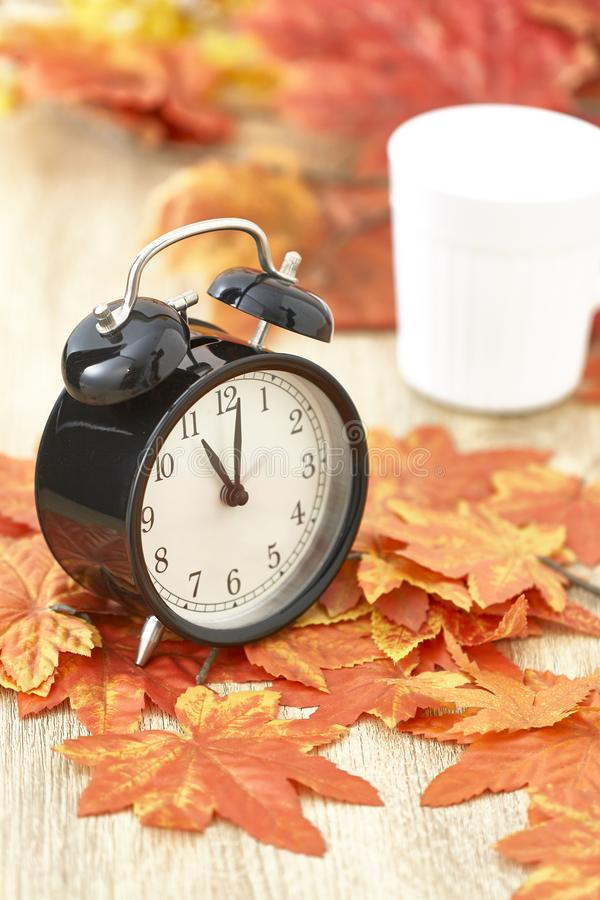Old clock on autumn leaves. On wooden table on natural background, day noon light Blank Space for text stock images