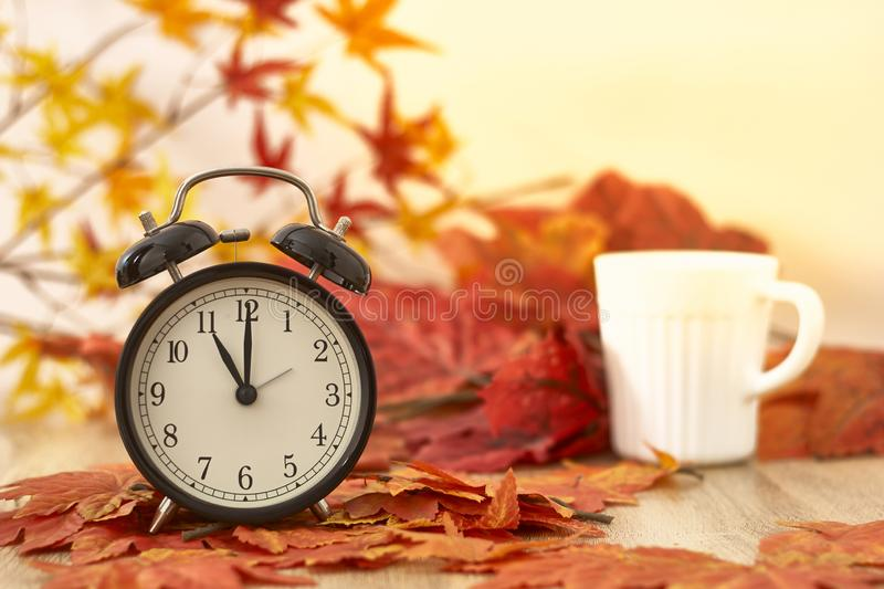 Old clock on autumn leaves. On wooden table on natural background, day noon light Blank Space for text stock photos