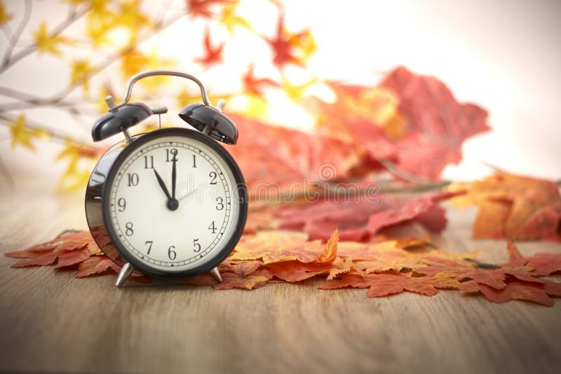 Old clock on autumn leaves. On wooden table on natural background, day noon light Blank Space for text stock image