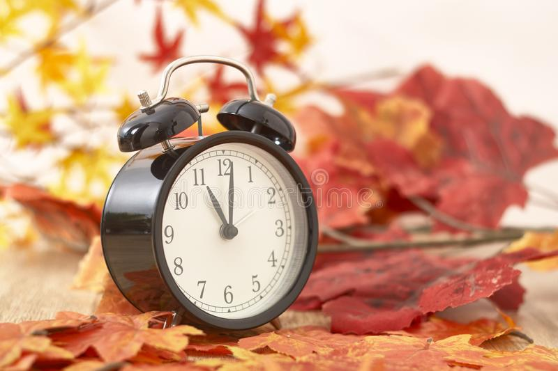Old clock on autumn leaves. On wooden table on natural background, day noon light Blank Space for text royalty free stock photo