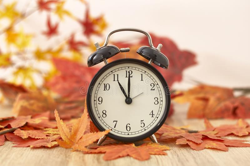 Old clock on autumn leaves. On wooden table on natural background, day noon light Blank Space for text royalty free stock photography