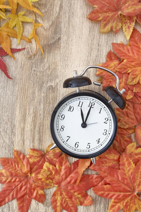 Old clock on autumn leaves. On wooden table on natural background, day noon light Blank Space for text stock photo