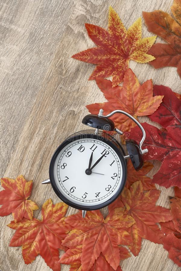 Old clock on autumn leaves. On wooden table on natural background, day noon light Blank Space for text royalty free stock images