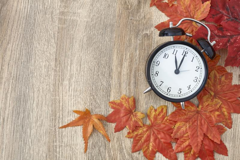Old clock on autumn leaves. On wooden table on natural background, day noon light Blank Space for text stock photography