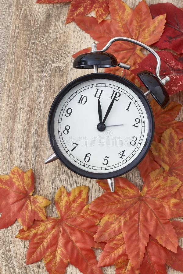Old clock on autumn leaves. On wooden table on natural background, day noon light Blank Space for text royalty free stock image