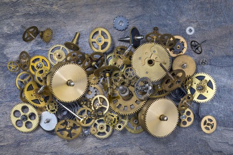 Old Clock Parts - Cogs, gears, wheels. Selection of dusty old brass clock parts stock image