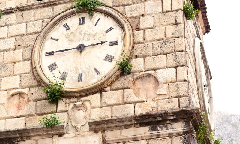 Old clock on a stone wall inside the town of Kotor stock photography