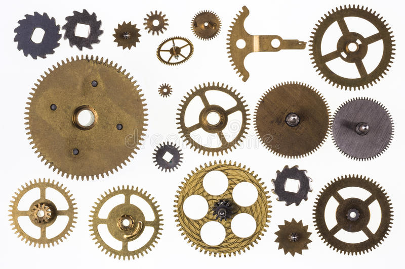 Old clockwork cogs and clock parts - Isolated. Old Technology - Selection of old brass clockwork clock parts - Isolated royalty free stock image