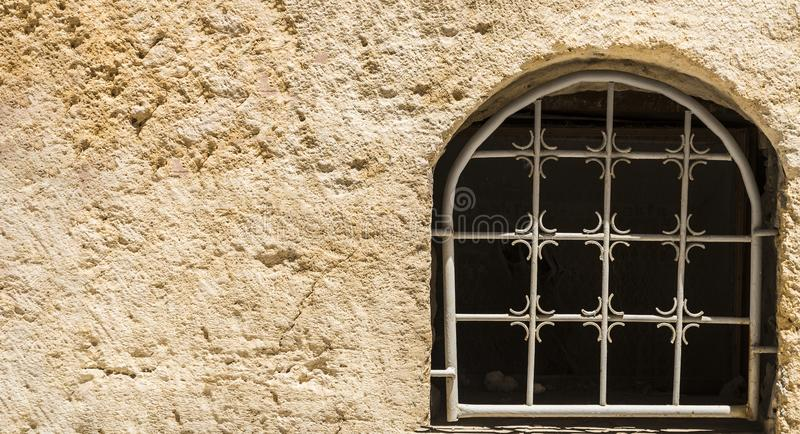 Old closed dirty window with metal bars on stone facade.Copy space.  stock photography