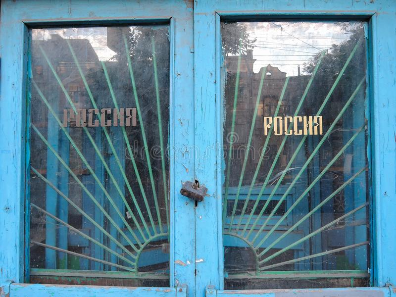 Old closed on a huge lock door with a wooden frame painted blue and cracked from time to time paint with the inscription Russia stock photo