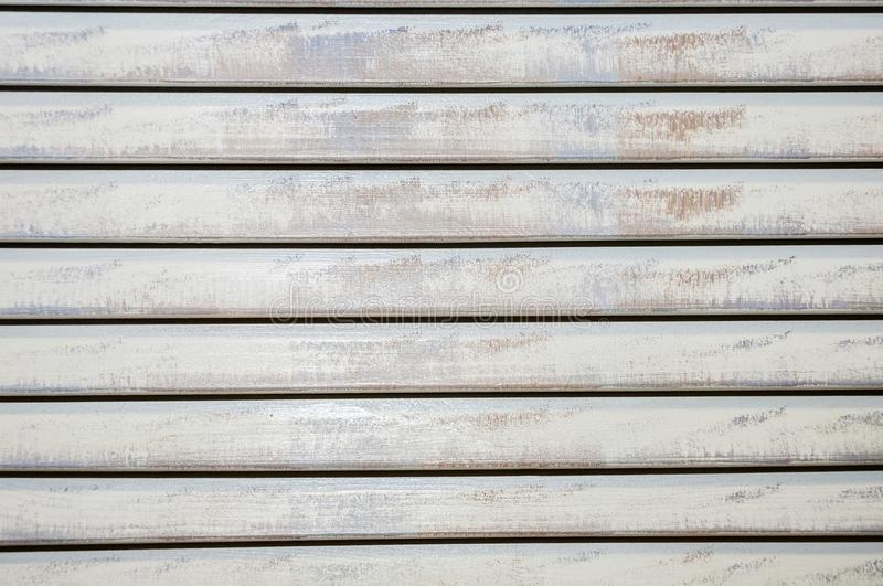 Old closed shabby horizontal long-painted wooden blinds stock photos