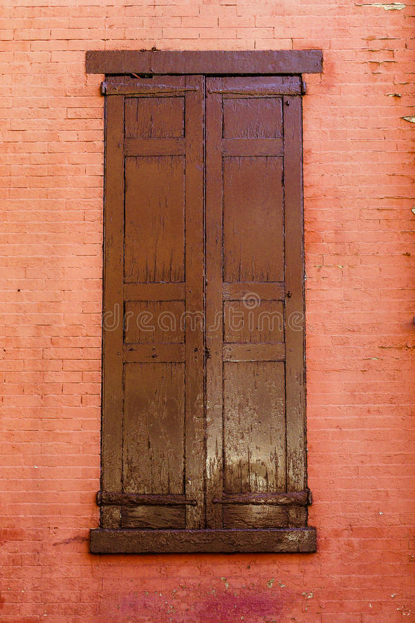 Old closed shutters on a red painted brick building stock images