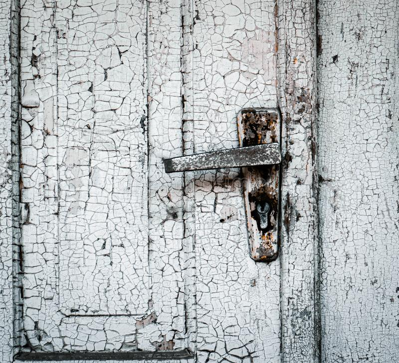 Old closed wood drift with a rusty iron door handle. The background is no free paint royalty free stock images
