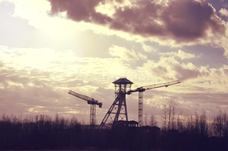 Old coal mine tower and cranes. Silhouettes of old coal mine tower and two cranes against dramatic skyscape in Genk, Belgium. Industrial construction and mining royalty free stock photos
