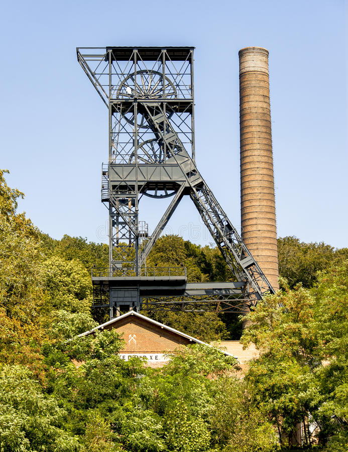 Old coal mine tower and industrial chimney in green environment royalty free stock photography